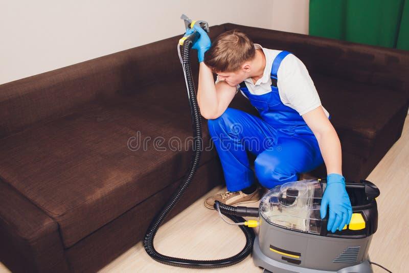 Homem novo cansado que senta-se no sofá na sala de visitas extrator, sofá do sofá, química, lavagem, limpeza trabalho azul foto de stock royalty free