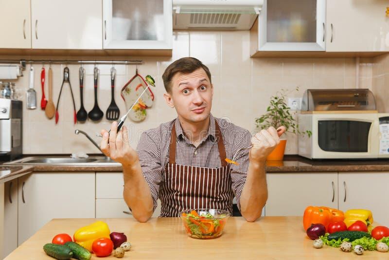 Homem novo caucasiano considerável, sentando-se na tabela Estilo de vida saudável Cozimento em casa Prepare o alimento imagem de stock