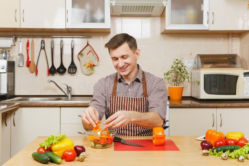 Homem novo caucasiano considerável, sentando-se na tabela Estilo de vida saudável Cozimento em casa Prepare o alimento imagem de stock royalty free