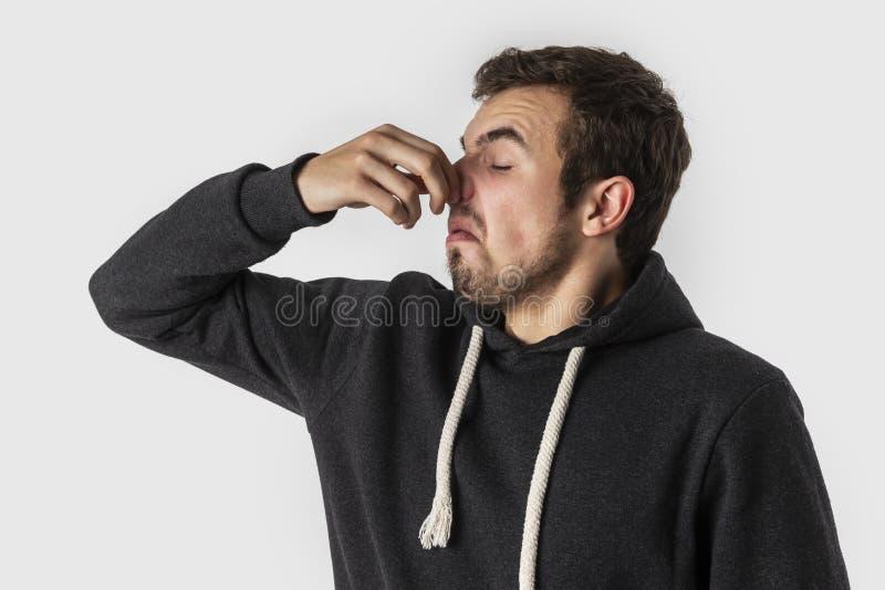 Homem novo caucasiano enojado que guarda seu nariz para evitar o cheiro mau Isolado no fundo branco fotos de stock royalty free