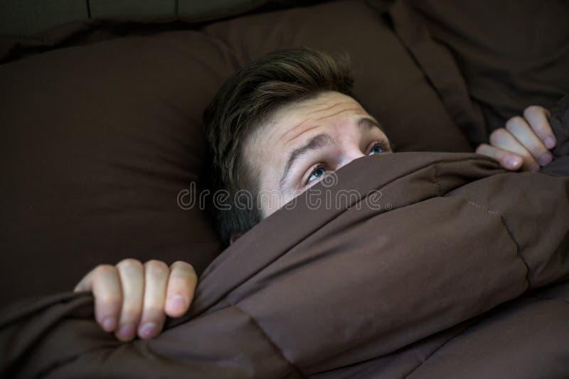 Homem novo caucasiano que esconde na cama sob a cobertura em casa imagem de stock