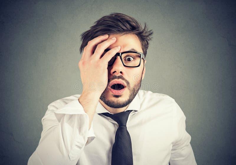 Homem novo chocado que olha a câmera imagens de stock