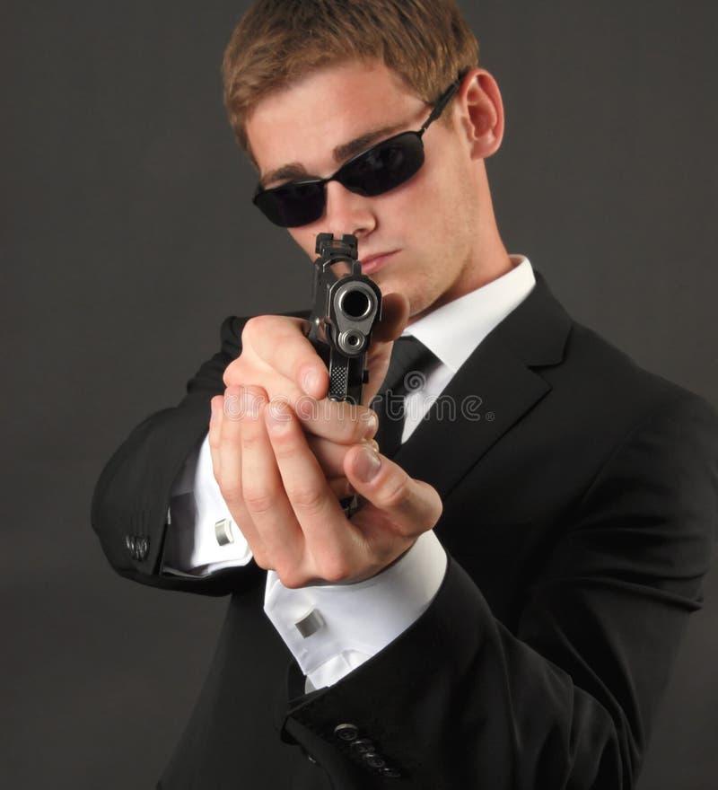 Homem novo com óculos de sol e um injetor imagem de stock