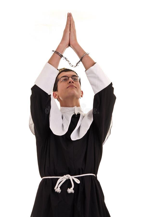 Homem novo com as algemas trajadas na freira para o divertimento, religiou engraçado fotos de stock