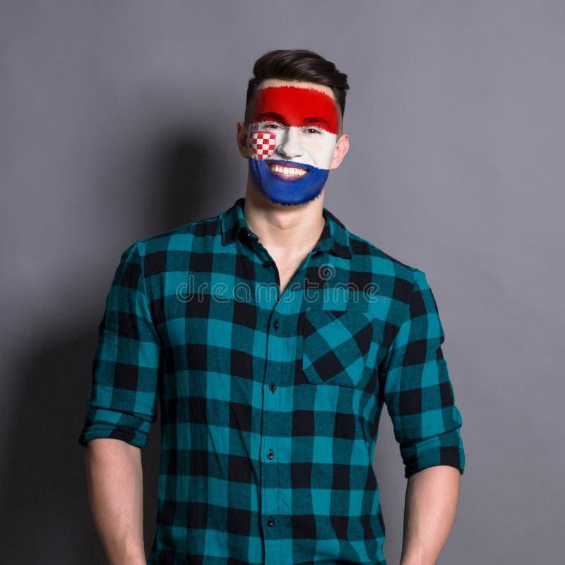 Homem novo com a bandeira da Croácia pintada em sua cara fotografia de stock