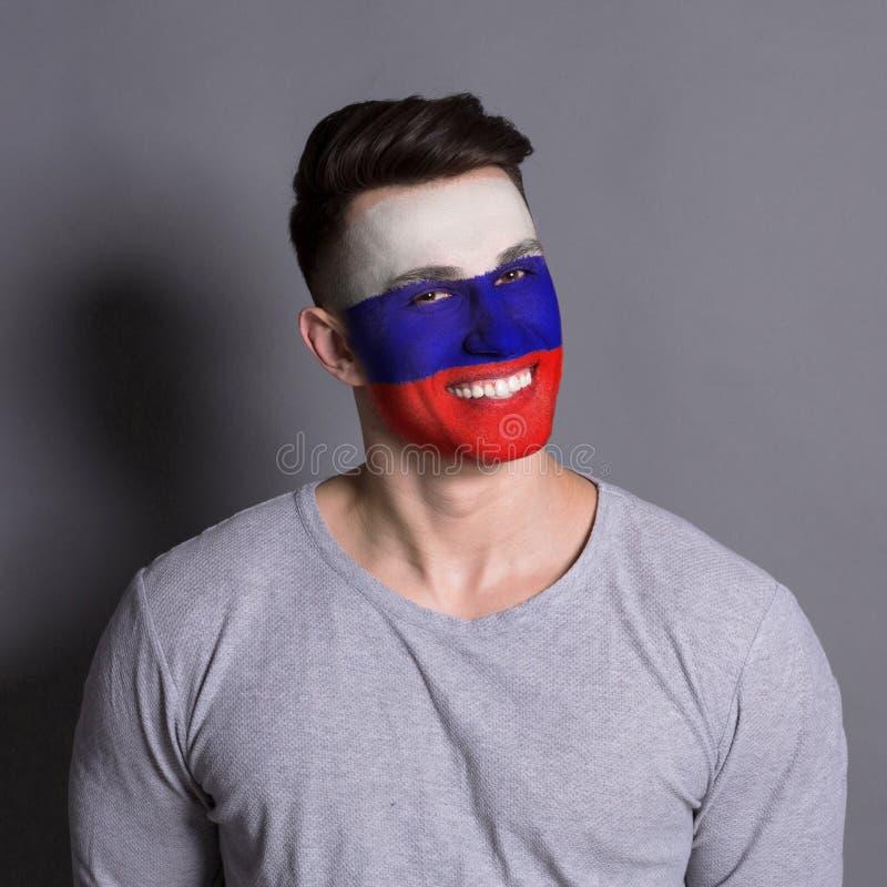 Homem novo com a bandeira do russo pintada em sua cara imagens de stock royalty free