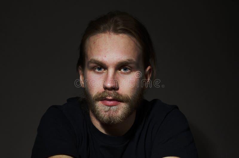 Homem novo com barba e bigode no fundo escuro imagens de stock royalty free