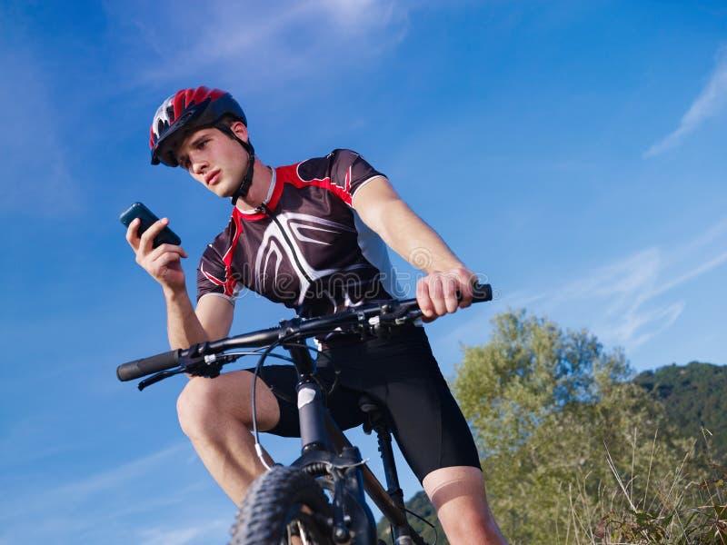Homem novo com a bicicleta de montanha da equitação do telefone fotos de stock royalty free