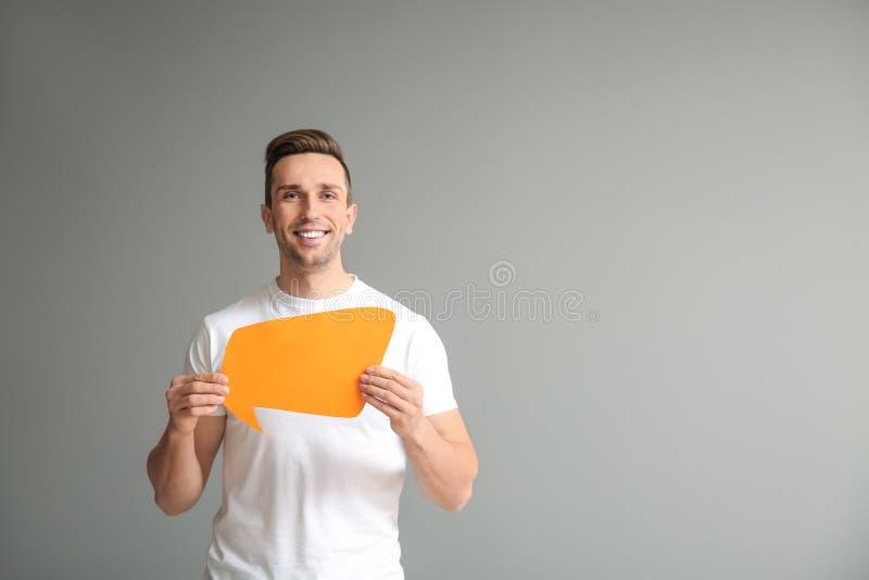 Homem novo com bolha do discurso no fundo cinzento fotos de stock royalty free