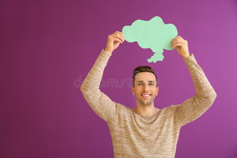 Homem novo com bolha do discurso no fundo da cor imagens de stock royalty free