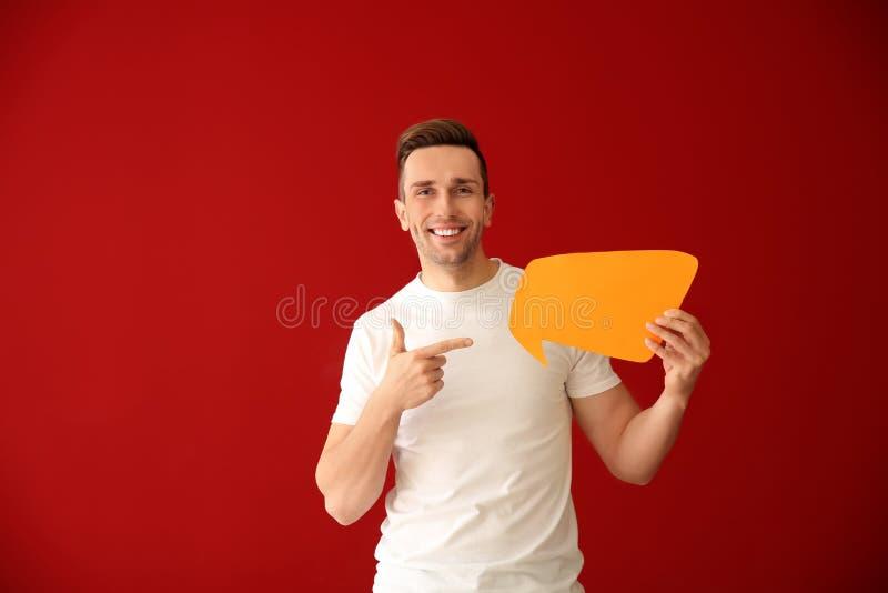 Homem novo com bolha do discurso no fundo da cor fotografia de stock