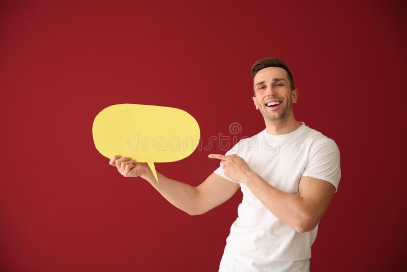 Homem novo com bolha do discurso no fundo da cor imagem de stock