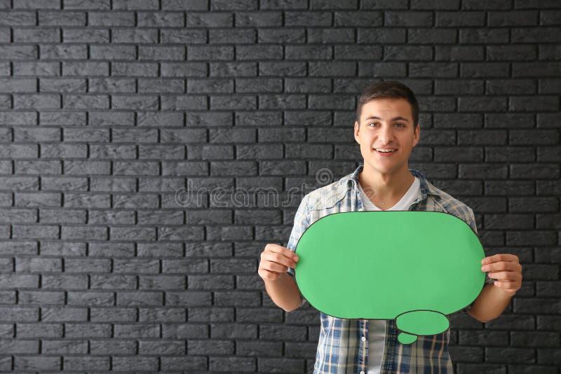 Homem novo com bolha do discurso no fundo escuro do tijolo fotografia de stock