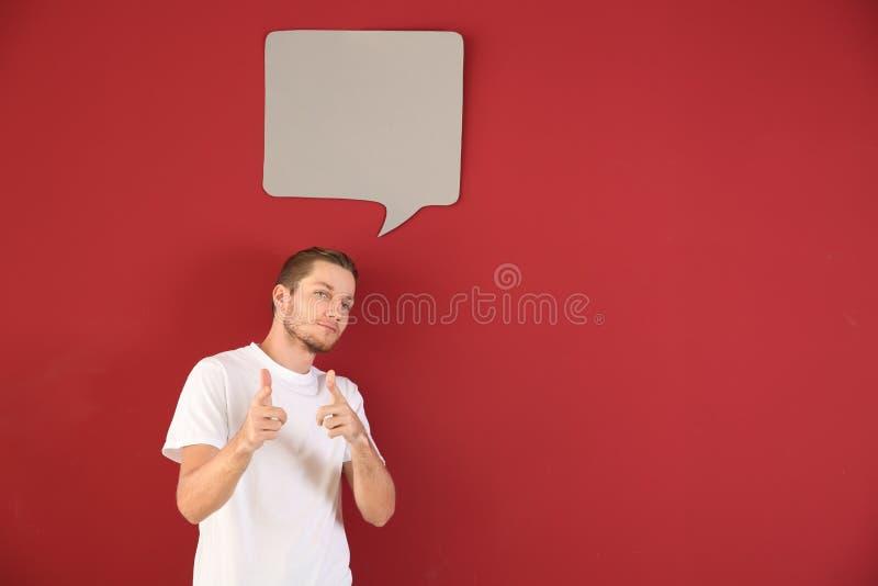 Homem novo com bolha vazia do discurso no fundo da cor fotos de stock