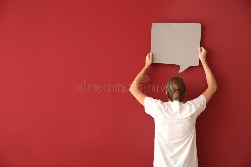 Homem novo com bolha vazia do discurso no fundo da cor foto de stock