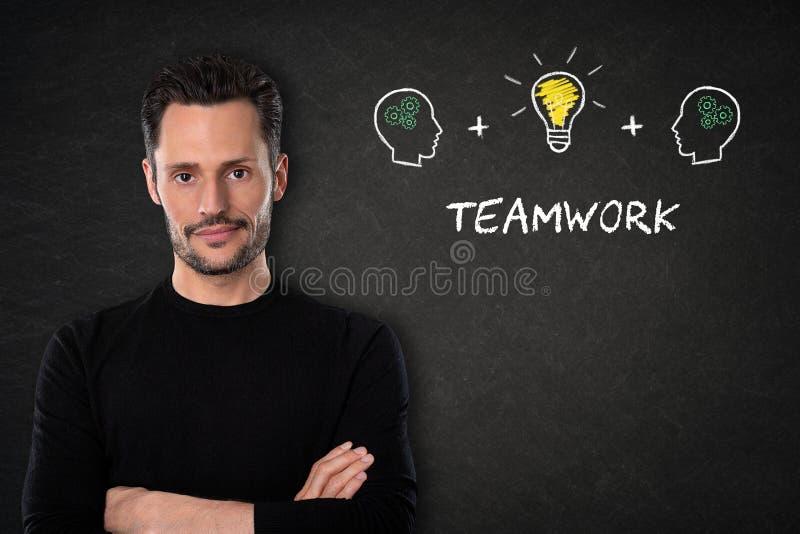 Homem novo com braços, texto 'dos trabalhos de equipe ', cabeças e ideia cruzados da ampola em um fundo do quadro-negro foto de stock
