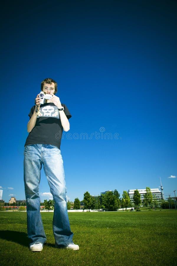 Homem novo com câmara de vídeo fotografia de stock