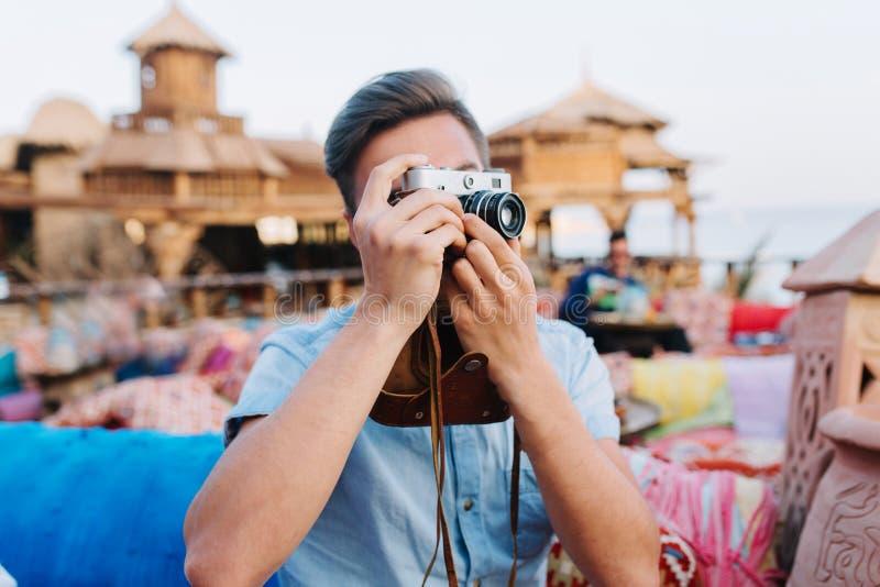 Homem novo com a câmera retro profissional que descansa no café exterior, amigos de espera Indivíduo que veste a camisa na moda d foto de stock royalty free
