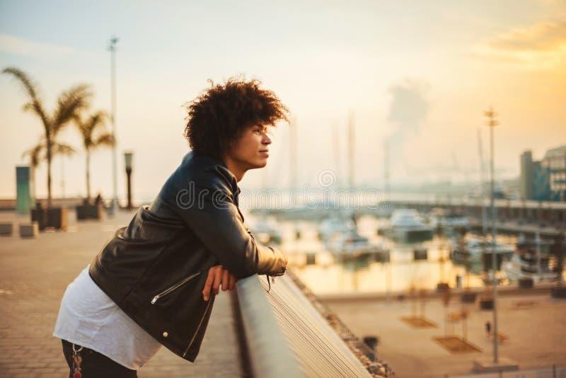 Homem novo com cabelo afro que aprecia a ideia do por do sol na cidade imagem de stock royalty free