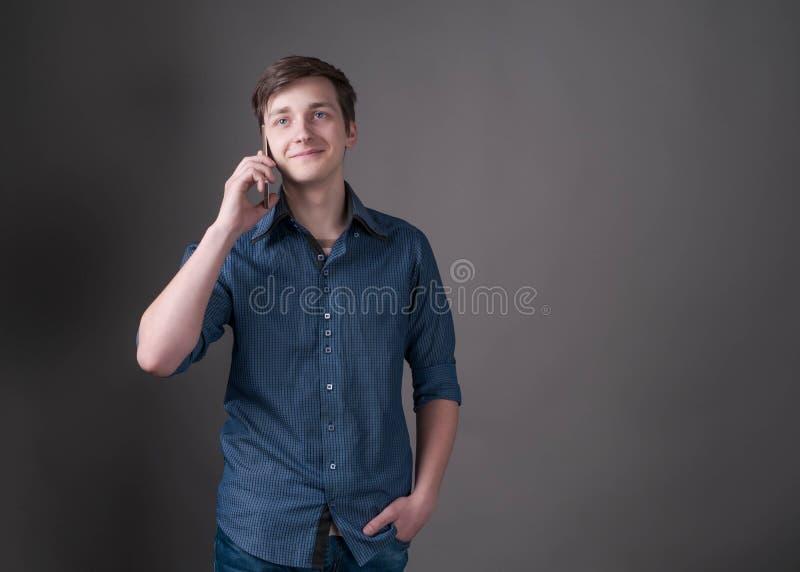 Homem novo com cabelo escuro na camisa azul, guardando a mão no bolso, falando no smartphone imagens de stock