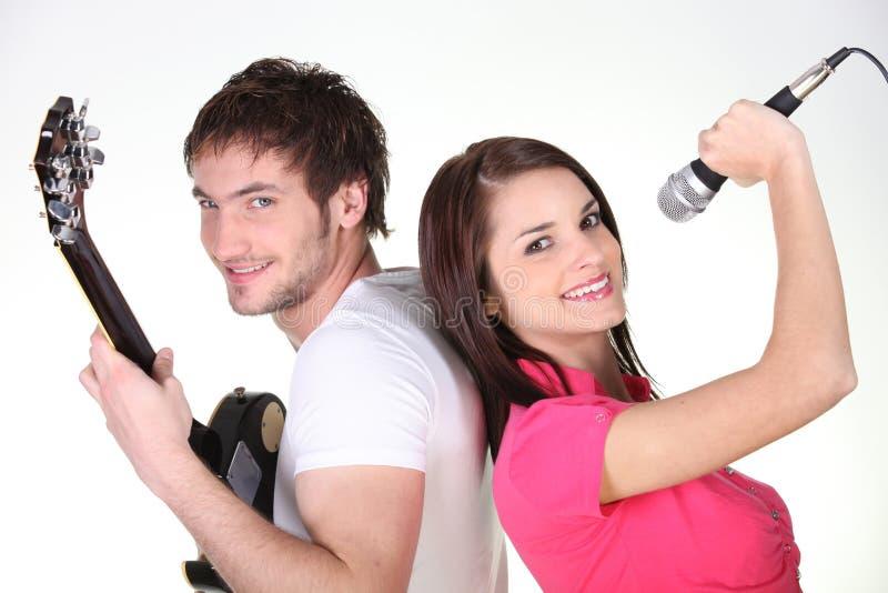Homem novo com canto da guitarra e da mulher fotos de stock