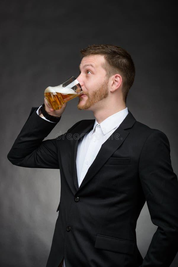 Homem novo com cerveja bebendo da barba imagens de stock royalty free