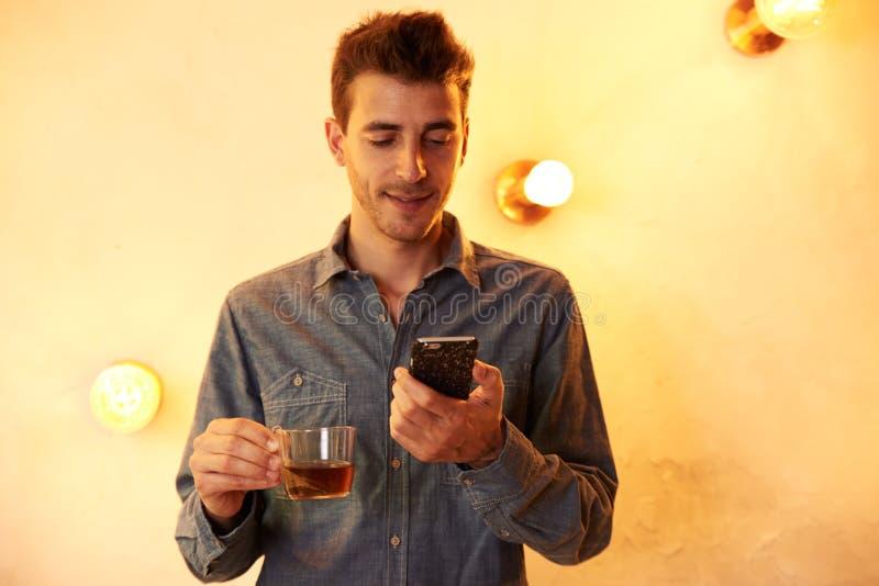 Homem novo com chá e telefone celular fotos de stock royalty free