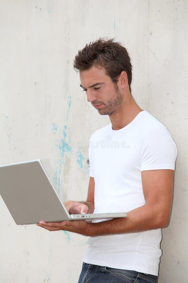 Homem novo com computador portátil foto de stock royalty free