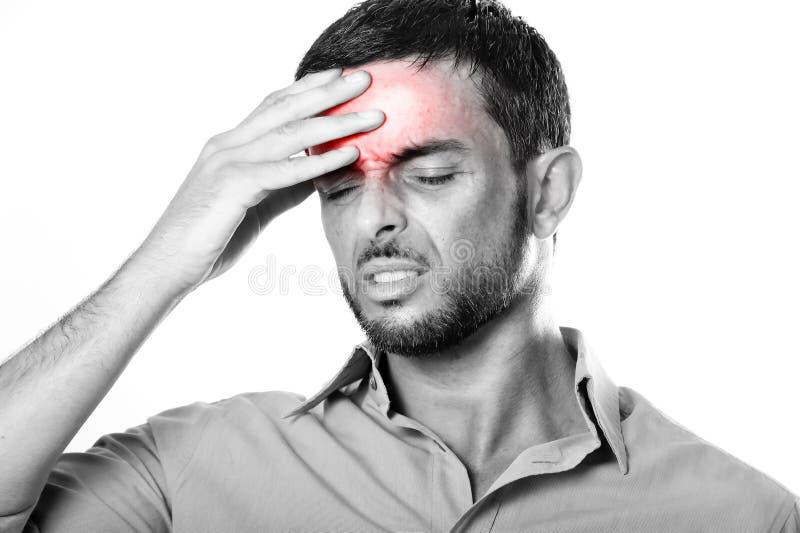 Homem novo com dor de cabeça e enxaqueca de sofrimento da barba na expressão da dor foto de stock