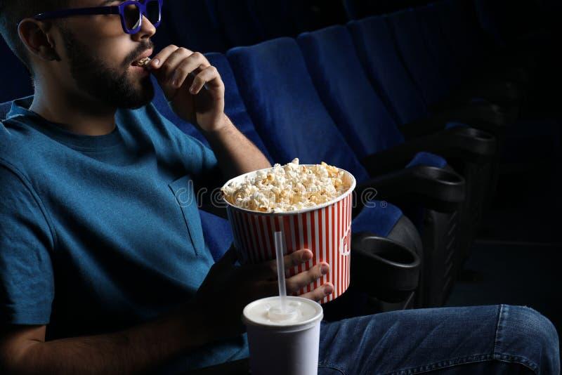 Homem novo com filme de observação da pipoca no cinema foto de stock