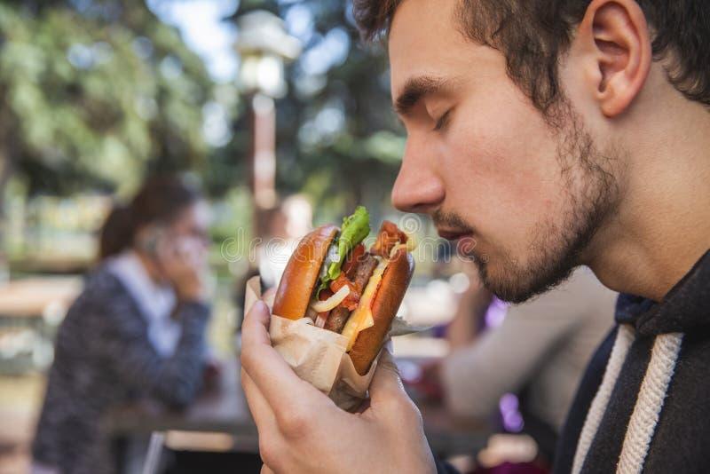 Homem novo com fome que aspira entusiasticamente seu hamburguer ao sentar-se no terraço do restauraunt Seus olhos são fechados imagem de stock