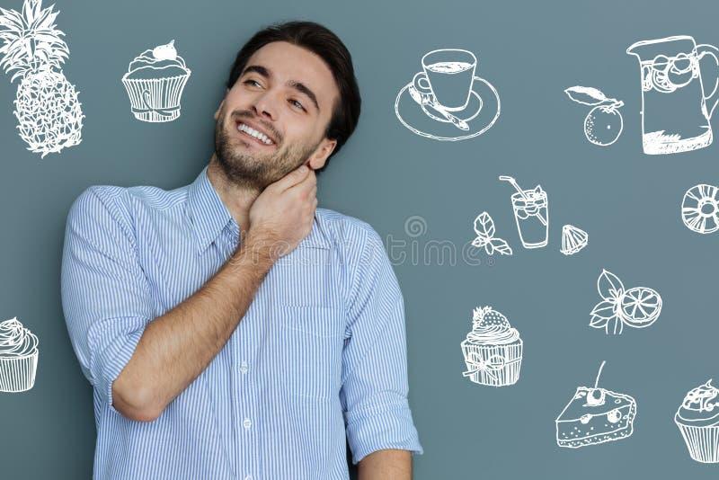 Homem novo com fome que sorri ao estar em um café novo imagens de stock royalty free