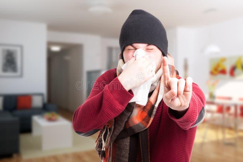 Homem novo com a gripe que funde seu nariz foto de stock royalty free