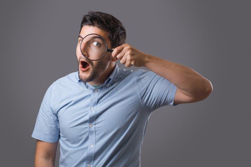 Homem novo com lente de aumento imagem de stock royalty free