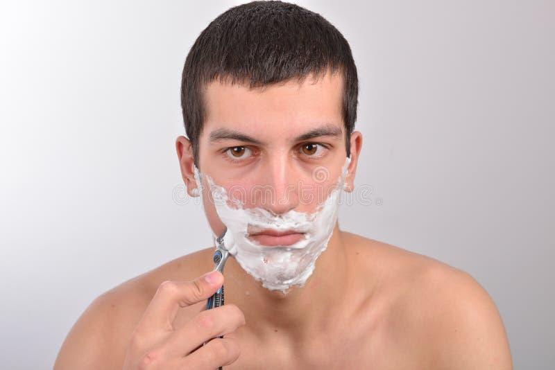 Homem novo com lotes do creme de rapagem no seu cara prepar imagem de stock royalty free