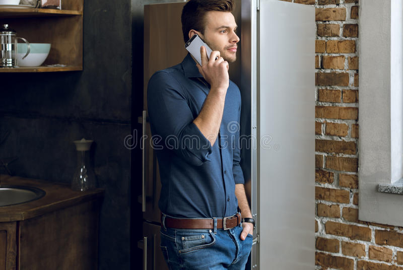 Homem novo com mão no bolso que fala no smartphone na cozinha foto de stock royalty free