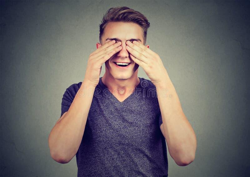 Homem novo com mãos nos olhos em antecipação a uma surpresa agradável imagem de stock