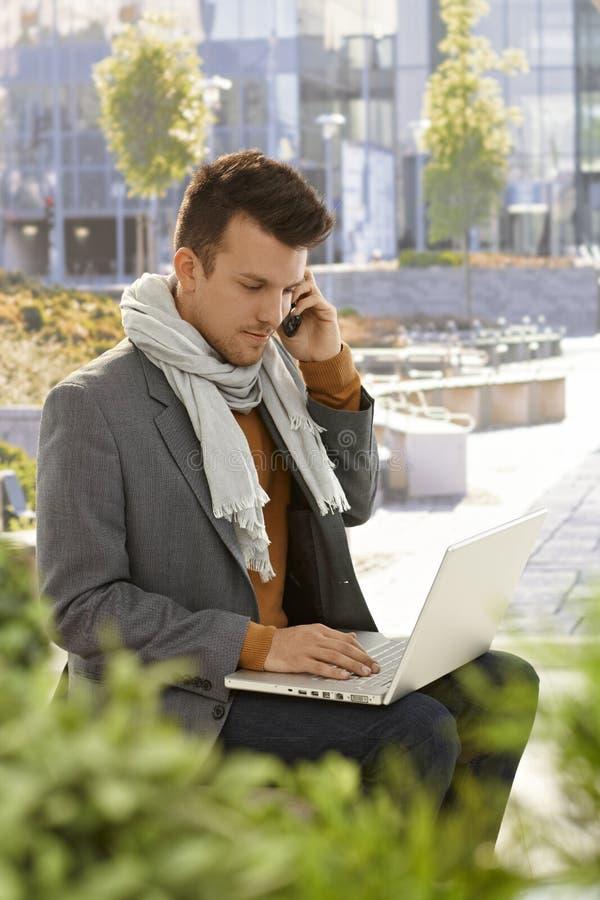 Homem novo com móbil e portátil fora foto de stock