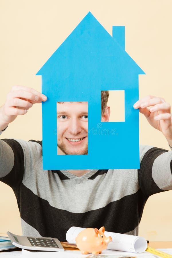 Homem novo com modelo de papel da casa imagem de stock royalty free