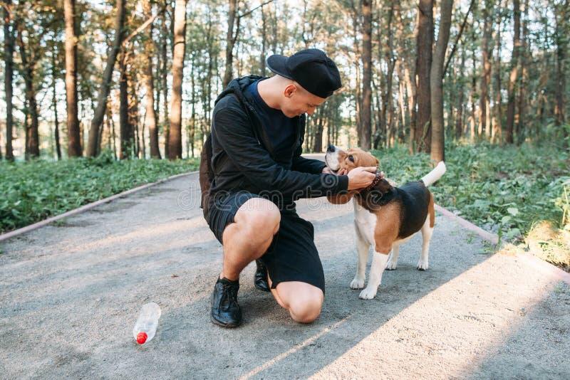Homem novo com o cão na estrada rural na floresta imagens de stock