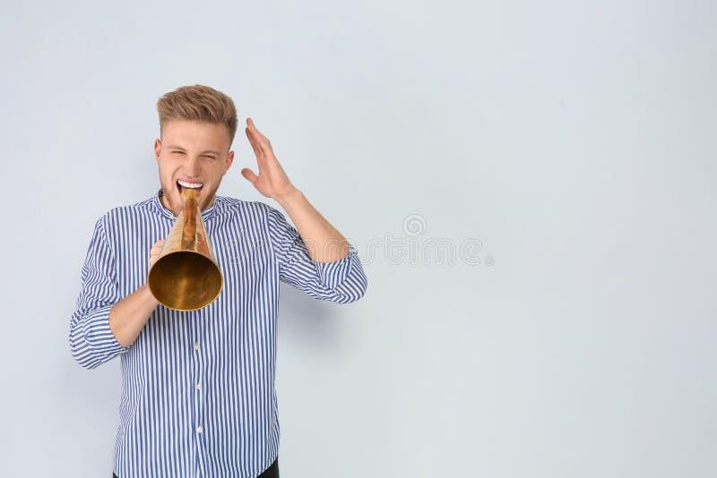 Homem novo com o megafone no fundo claro imagem de stock royalty free