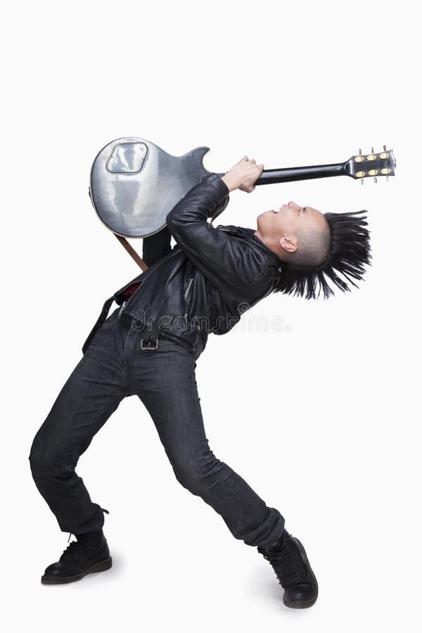 Homem novo com o Mohawk punk que joga a guitarra fotografia de stock royalty free