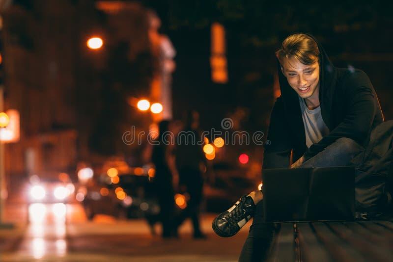 Homem novo com o portátil na cidade da noite imagens de stock royalty free