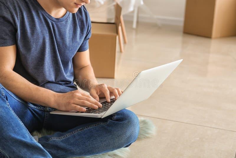 Homem novo com o portátil que senta-se no assoalho após mover-se na casa nova fotografia de stock