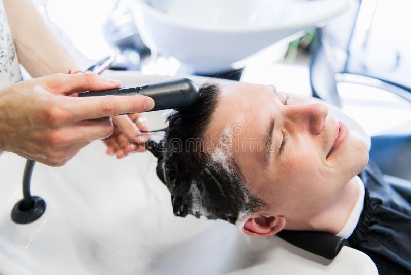 Homem novo com o problema da queda de cabelo que obtém seu cabelo lavado antes de receber a injeção imagem de stock royalty free
