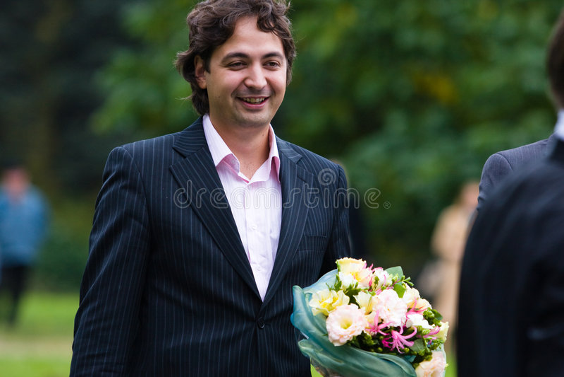 Homem novo com o ramalhete bonito das flores foto de stock