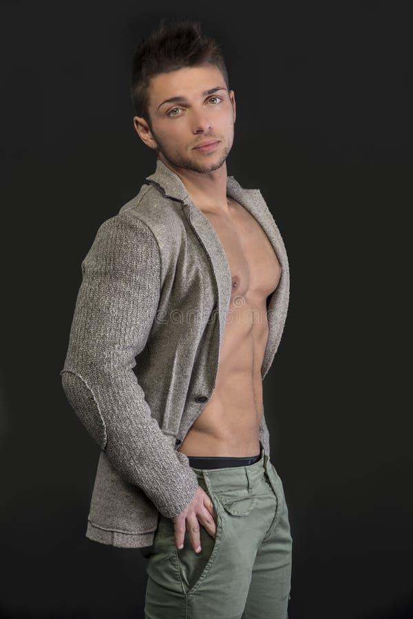 Homem novo com o revestimento aberto no torso muscular imagem de stock royalty free