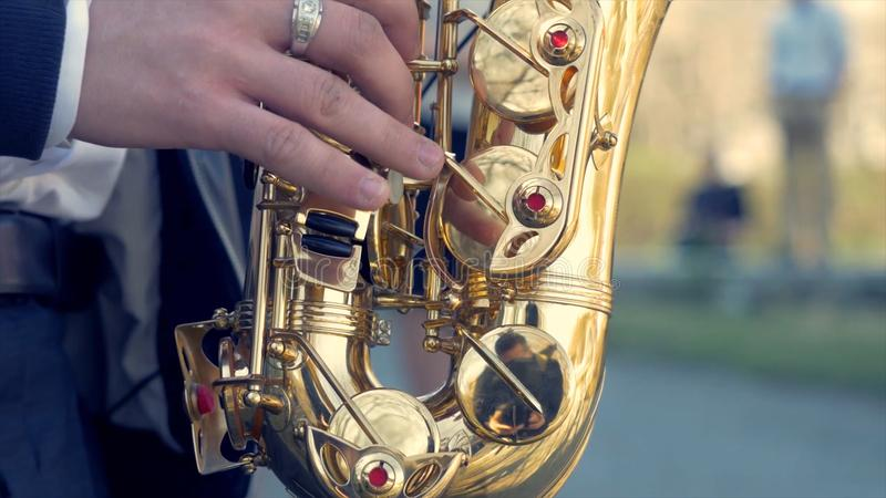 Homem novo com o saxofone fora perto da parede pintada velha Músico expressivo novo que joga o saxofone Arte e foto de stock
