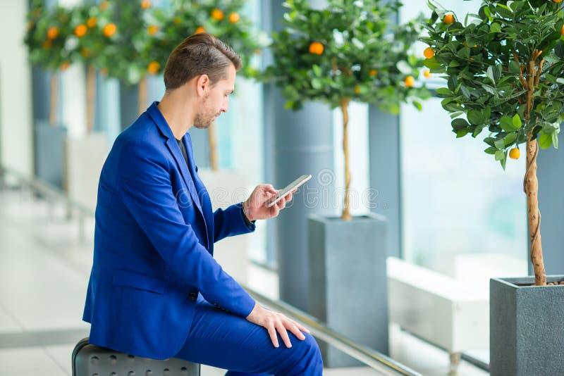 Homem novo com o telefone celular no aeroporto ao esperar o embarque Revestimento vestindo do terno do menino novo ocasional fotografia de stock