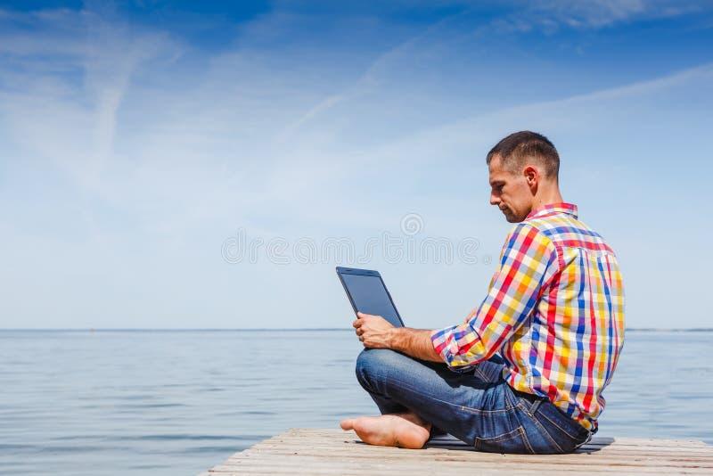 Homem novo com o trabalho do portátil exterior fotografia de stock royalty free